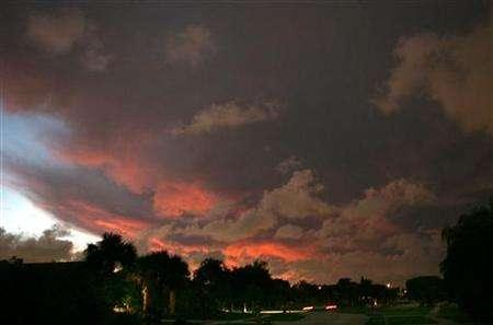 The sun sets through storm clouds over a neighborhood in Palm Beach County, Florida, October 22, 2005. Florida is expected to impose strict new air-pollution standards that aim to reduce greenhouse-gas emissions by 80 percent of 1990 levels by 2050, according to draft regulations released on Wednesday. REUTERS/Marc Serota