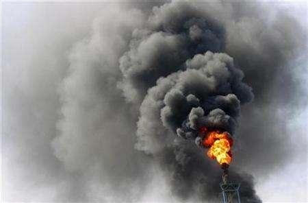 Fire and smoke are seen at a oil refinery in Lanzhou, capital of northwest China's Gansu province, May 31, 2007. Some lucrative projects which cut greenhouse gas emissions in developing countries are still getting U.N.-approval to sell carbon credits even though the cuts may have happened anyway, a U.N. official said. REUTERS/Stringer