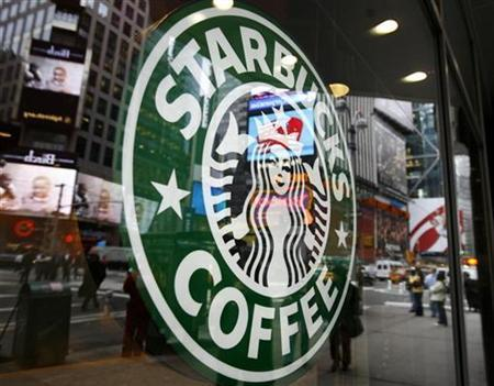 The Starbucks logo is seen outside a coffee-shop in New York's Times Square March 15, 2007. Starbucks Corp. will raise prices at its U.S. coffee shops by about 9 cents a drink next week to help offset rising costs for commodities such as milk and energy, a spokesman said on Monday. REUTERS/Shannon Stapleton