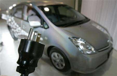 A Toyota Motor Corp.'s employee holds up a three-prong plug for a photo during the unveiling of a plug-in hybrid vehicle in Tokyo July 25, 2007. The vehicle, certified for public road-use by Japan's Ministry of Land Infrastructure and Transport, is able to travel at a maximum speed of 100km (62 miles) per hour and Toyota estimates the vehicle to run 13km (8 miles) under electric vehicle mode by charging three to four hours with an ordinary electric wall socket. REUTERS/Yuriko Nakao
