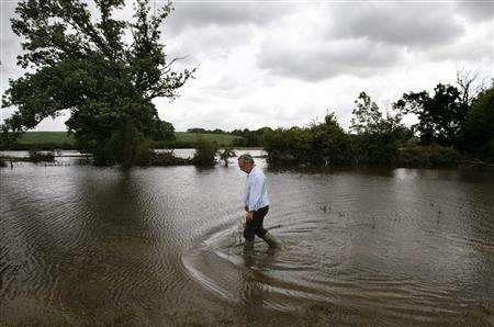 Farmer Derek Roberts walks through his flooded meadow in Ripple, central England, July 27, 2007. REUTERS/Darren Staples