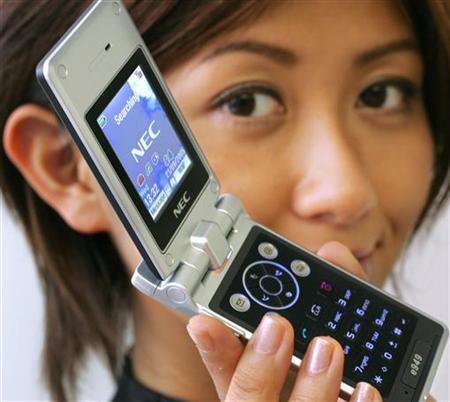 A model displays a cell phone in Tokyo in this September 21, 2005 file photo. The light from the cell phone screens allowed surgeons to complete an emergency appendix operation during a blackout in a city in central Argentina, reports said on Saturday. REUTERS/Yuriko Nakao