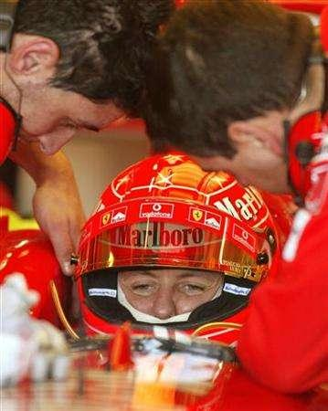 In this file photo former Formula One champion Michael Scumacher looks on as team mechanics work on his car during a testing session at the Ricardo Tormo race track near Valencia February 3, 2005. Schumacher can add the unofficial title of Germany's fastest taxi driver to his other achievements after taking over behind the wheel to get his family to the airport on time. REUTERS/Heino Kalis PH/acm
