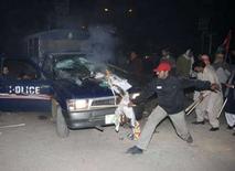 <p>Сторонники убитой Беназир Бхутто, лидера оппозиции Пакистана, нападают на полицейскую машину в время беспорядков в Лахоре 27 декабря , 2007 года.Пакистан, ключевой азиатский союзник США в объявленной Вашингтоном войне с терроризмом, вторые сутки охвачен насилием после убийства лидера оппозиции и экс-премьера Беназир Бхутто. На улицы пакистанских городов вышли тысячи сторонников Бхутто и ее партии, которые схлестнулись в яростных схватках с полицией, пытающейся разогнать беснующуюся толпу. (REUTERS/Mohsin Raza)</p>