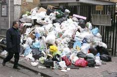 <p>Un uomo a Napoli di fianco a un cumulo di spazzatura. REUTERS/Ciro de Luca/AGN (ITALY)</p>