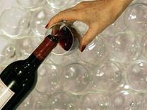 <p>Una donna si fa versare del vino rosso nel bicchiere. REUTERS/Regis Duvignau (FRANCE)</p>