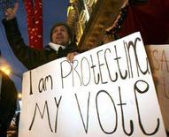 """<p>Сторонник грузинской оппозиции держит плакат с надписью """"Я защищаю свой голос"""" во время митинга в Тбилиси 8 января 2008 года. Оппозиция в Грузии не согласна с предварительными итогами досрочных президентских выборов, согласно которым победил бывший президент Михаил Саакашвили, и требует второго тура, грозя массовыми акциями протеста. (REUTERS/David Mdzinarishvili)</p>"""