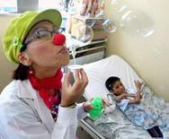 <p>Visite d'un clown à un enfant hospitalisé à Lima, au Pérou. Après la publication d'une étude britannique suggérant que les enfants n'aiment pas les clowns et en ont même souvent peur, les amuseurs à nez rouge intervenant dans les hôpitaux pédiatriques ont défendu leur rôle auprès des enfants malades. /Photo d'archives/REUTERS/Pilar Olivares</p>