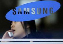 <p>Una donna al telefono seminascosta dal logo di Samsung. REUTERS/Han Jae-Ho (SOUTH KOREA)</p>