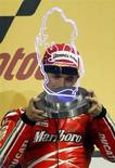 <p>Il pilota della Ducati Casey Stoner festeggia sul gradino più alto del podio del Gran Premio di MotoGP del Qatar. REUTERS/Fadi Al-Assaad (QATAR)</p>