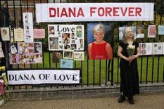 <p>Una donna regge un mazzo di fiori fuori dalla residenza della principessa Diana addobbata di decorazioni alla sua memoria. Foto d'archivio. REUTERS/Kieran Doherty (BRITAIN)</p>