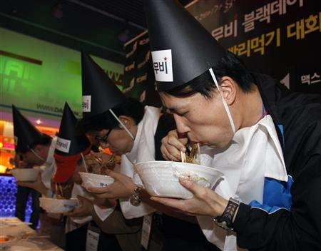 Participants eat Jajangmyeon, Chinese-style noodles topped with a thick sauce of black bean paste, at a speed eating competition, sponsored by an online company, for movie tickets at a movie theatre in Seoul April 14, 2008. It was a Black Day for love in South Korea on Monday with lonely hearts trying to ease their pain by diving head first into bowls of noodles. REUTERS/Lee Jae-Won