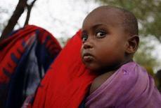 <p>Un bimbo portato sulla schiena dalla madre a Mandera, in Kenya. REUTERS/Radu Sigheti (KENYA)</p>