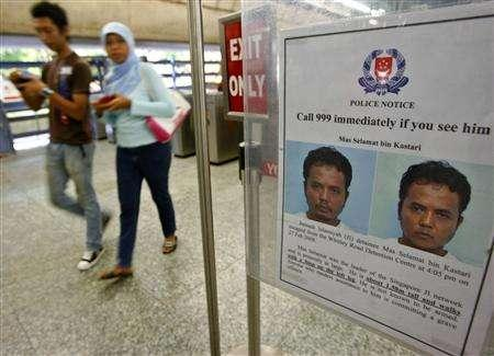 Commuters walk past a poster of suspected Islamic militant Mas Selamat bin Kastari at an MRT train station in Singapore April 21, 2008. Singapore said on Monday that a suspected Islamic militant managed to escape from a detention centre two months ago mainly because of an unlocked window in the toilet -- and fled without his trousers. REUTERS/Vivek Prakash