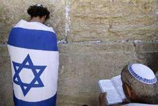 <p>Израильский юноша, завернувшись в национальный флаг, молится у Западной стены Иерусалима 8 мая 2008 года во время празднования Дня независимости и 60-летнего юбилея создания страны (REUTERS/Yannis Behrakis)</p>