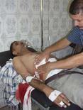 <p>Врач оказывает помощь мужчине, раненному в результате атаки экстремиста в Бакубе 27 мая 2008 года. Как минимум 14 новобранцев иракской полиции и двое офицеров погибли в результате взрыва, устроенного экстремистом - смертником в четверг, сообщили источники в полиции и вооруженных силах Ирака. (REUTERS/Stringer)</p>