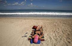 <p>Una turista prende il sole in spiaggia. REUTERS/Murdani Usman</p>