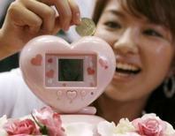 """<p>L'amour ne s'achète pas mais les Japonaises pourront bientôt joindre l'utile à l'agréable grâce à une tirelire électronique qui leur permettra de s'offrir une romance virtuelle avec un personnage d'animation tout en faisant fructifier leurs économies. L'""""Ikemenbank"""", ou """"tirelire beau garçon"""", un appareil électronique en forme de coeur et équipé d'un écran LCD, sera lancée dans les boutiques japonaises le 6 septembre, au prix de 4.935 yens (29,6 euros). /Photo prise le 19 juin 2008/REUTERS/Toru Hanai</p>"""