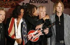 """<p>Activision lance """"Guitar Hero: Aerosmith"""", un nouvel épisode de son jeu vidéo à succès qui permettra aux fans du groupe de hard rock de se glisser dans la peau de Steven Tyler (au centre) ou de ses acolytes, à l'aide du célèbre accessoire imitant un manche de guitare et décoré pour l'occasion aux couleurs du groupe. /Photo prise le 27 juin 2008/REUTERS/Lucas Jackson</p>"""