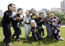 <p>Attivisti dell'organizzazione britannica Oxfam indossano maschere con i volti del leader del G8 a Sapporo, in Giappone in vista del vertice di Hokkaido. REUTERS/Yuriko Nakao</p>