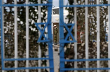 An Israeli soldier stands behind a gate at the Rosh Hanikra border crossing with Lebanon, in northern Israel, July 15, 2008. REUTERS/Ronen Zvulun