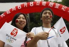 <p>Un couple de jeunes mariés après la cérémonie à Pékin. Au moins 16.400 couples dans la capitale, et des milliers d'autres dans le reste du pays, ont choisi de s'unir le huitième jour du huitième mois de l'année 2008, une combinaison de bon augure en Chine où le 8 est un chiffre porte-bonheur. Les Jeux olympiques s'ouvrent également ce vendredi. /Photo prise le 8 août 2008/REUTERS/Laszlo Balogh</p>