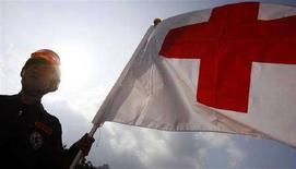 """<p>Человек с флагом Красного Креста в Тайбэе 16 мая 2008 года. Грузия и Южная Осетия должны открыть """"гуманитарный коридор"""" и позволить эвакуировать пострадавших во время военных действий, заявил Международный комитет Красного Креста. (REUTERS/Nicky Loh)</p>"""