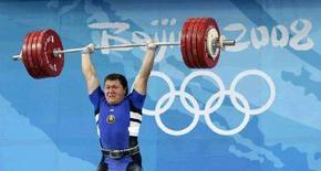 <p>Белорусский штангист Андрей Арамнов с весом 236 килограмм на Олимпиаде в Пекине, 18 августа 2008 года. Арамнов в понедельник завоевал золотую медаль в весовой категории до 105 килограммов, установив мировой рекорд в толчке, подняв 200-килограммовый вес. REUTERS/Jason Lee (CHINA)</p>