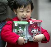 """<p>Bambino stringe due nuovi pupazzetti """"Fuwa"""", mascotte delle Olimpiadi di Pechino 2008. REUTERS/Stringer</p>"""