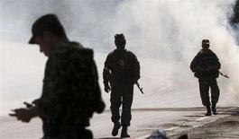 <p>Российские военнослужащие идут по дороге после того, как дымовыми шашками обозначили место посадки вертолетов близ Каспи 19 августа 2008 года. Российские войска начали выход из грузинского города Гори в направлении Владикавказа, передал корреспондент Рейтер с места событий. (REUTERS/Adrees Latif)</p>