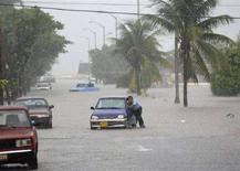 """<p>Человек толкает автомобиль на затопленой улице Гаваны 26 августа 2008 года. Набирающий силу тропический шторм """"Густав"""" движется на юг и может затронуть южную часть острова Ямайка и западную часть Кубы до того, как уже в качестве мощного урагана достигнет нефтяных месторождений Мексиканского залива. REUTERS/Claudia Daut</p>"""