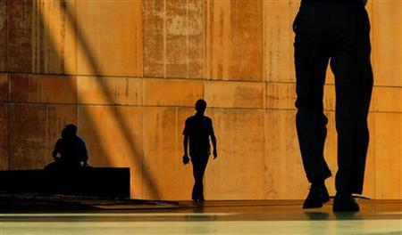 Workers in London's financial district are silhouetted against a wall during a heat wave, August 4, 2003. REUTERS/Peter Macdiarmid