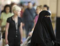 <p>A veiled woman looks on as shoppers walk by in a shopping mall in Dubai in this picture taken September 23, 2008. Sex on the beach or drunken trysts may not raise eyebrows in many cities, but a recent case in Dubai has exposed a growing cultural divide between native Muslims and Western residents seeking fun in the sun. Picture taken September 23. To match feature DUBAI-SEX/ REUTERS/Morteza Nikoubazl</p>