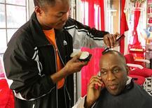 <p>Homem conversa por celular em barbearia na Cidade do Cabo. O número de usuários de celular em todo o mundo deve atingir 4 bilhões até o final deste ano, número que, em tese, faria com que a porcentagem de habitantes do planeta com um telefone móvel alcance os 61 por cento ante 12 por cento em 2000, informa a União Internacional de Telecomunicações (UIT), da Organização das Nações Unidas (ONU).</p>