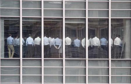 Lehman Brothers employees stand in a meeting room in the financial district of Canary Wharf in London, September 11, 2008. REUTERS/Kevin Coombs