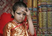 "<p>Shreeya Bajracharya adjusts her ""third eye"" while posing for the photographer as the newly appointed Goddess Kumari at Bhaktapur in Kathmandu September 29, 2008. REUTERS/Gopal Chitrakar</p>"