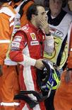 <p>O piloto de Fórmula 1, Felipe Massa, se afasta de seu veículo após derrota no Grande Prêmio de Cingapura em 28 de setembro. A Ferrari vai revisar seu sistema eletrônico de luzes no pitstop depois que um erro humano custou a vitória a Massa no Grande Prêmio de Cingapura, no domingo, causando um grande golpe nas esperanças de título do piloto brasileiro. REUTERS/Russell Boyce</p>
