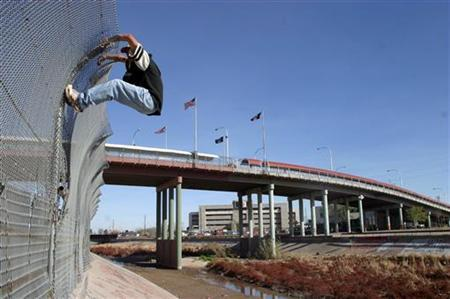 A migrant tries to cross into the U.S. from the Mexican border town of Ciudad Juarez, under the bridge that connects the border city with El Paso March 6, 2006. REUTERS/Stringer