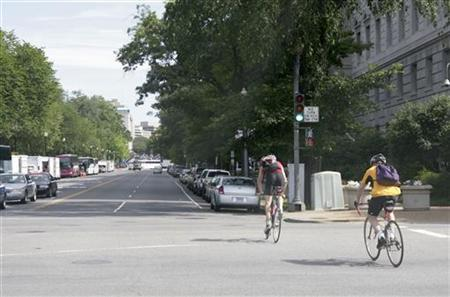 Two cyclists ride along the 15th Street North West in Washington June 11, 2008. REUTERS/Hyungwon Kang