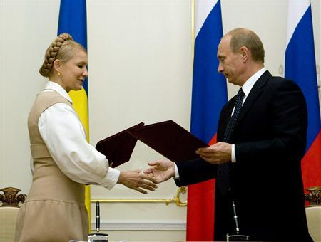 Russian Prime Minister Vladimir Putin (R) exchange documents with his Ukrainian counterpart Yulia Tymoshenko during a signing ceremony in the Novo-Ogaryovo residence outside Moscow October 2, 2008. Russia and Ukraine agreed on Thursday to set a step-by-step, three-year period for Ukraine's transition to purchases of Russian natural gas at market prices, Tymoshenko said. REUTERS/Sergei Karpukhin