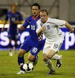 <p>O atacante Wayne Rooney ao lado do croata Niko Kovac em partida pela Seleção Inglesa. Atualmente lesionado, Rooney se juntará à seleção da Inglaterra na próxima semana com as bênçãos de Alex Ferguson, caso se recupere a tempo. Imagem de arquivo. 10 de setembro.REUTERS/Nikola Solic</p>