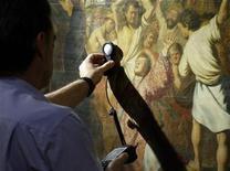 """<p>Un trabajador mide la cantidad de luz sobre una obra del artista Rembrandt durante una visita de la prensa para la exhibición """"Rembrandt. Pintor de historias"""", en el Museo del Prado, 10 oct 2008. El Museo del Prado inaugurará el próximo miércoles una exposición monográfica titulada """"Rembrandt. Pintor de historias"""", centrada en el género de la narrativa visual del artista holandés. REUTERS/Susana Vera (ESPANA)</p>"""