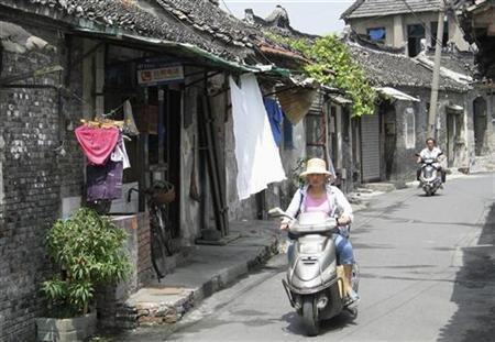 A woman rides a scooter down an alley in Taizhou, China, August 20, 2007. REUTERS/Ben Blanchard