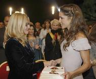 <p>Jordan's Queen Rania (R) presents the Al Hussein Medal to Nicoletta Mantovani Pavarotti, wife of Luciano Pavarotti, during a tribute charity concert and memorial ceremony for the late Italian tenor in Petra October 12, 2008. Proceeds from the concert will generate funds for projects in Afghanistan by the U.N. refugee agency and the U.N. World Food Programme, as well as for the Petra archaeological site 180 km (120 miles) south of Amman. Jordan's King Abdullah on Sunday bestowed upon Luciano Pavarotti the Al Hussein Medal – First Order for his contributions and his humanitarian role as a peace ambassador of the U.N. REUTERS/Naser Ayoub (JORDAN)</p>