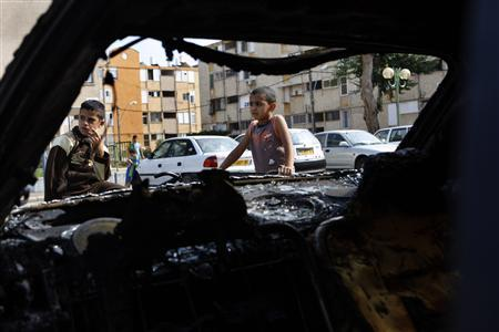 Israeli-Arab boys stand near a burnt car in the northern coastal city of Acre October 12, 2008. Israeli Prime Minister Ehud Olmert told police on Sunday to show ''zero tolerance'' towards rioters after a fourth night of violence between Arabs and Jews in Acre. REUTERS/Ammar Awad (
