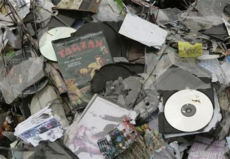 Crushed pirated CDs and DVDs of music, films and software seized from street sellers and shops are seen in Bucharest May 4, 2007. REUTERS/Bogdan Cristel