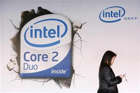 A woman checks her mobile phone as she walks past an Intel Core Duo advertisement outside a computer shop in Beijing March 26, 2007. REUTERS/Claro Cortes IV