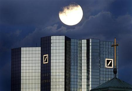 A rising full moon is seen over the distinctive twin towers of Germany's Deutsche Bank headquarters in Frankfurt January 28, 2002. REUTERS/Kai Pfaffenbach REUTERS