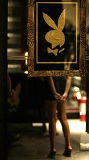 A woman stands behind a Playboy symbol at the entrance during a news launch of the Playboy magazine in a hotel in Manila April 2, 2008. REUTERS/John Javellana