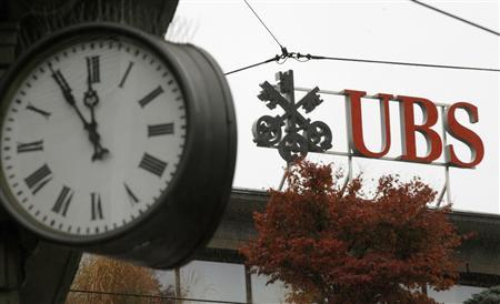 A clock is seen beside the logo of Swiss bank UBS at the Paradeplatz square in Zurich October 16, 2008. REUTERS/Arnd Wiegmann